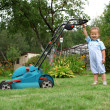 Little Boy Gardener mowing the lawn — Stock fotografie
