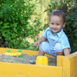 Baby plays with toys in sandbox — Stock Photo