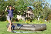 Boy inflate boat and show power — Stock Photo