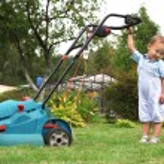 Little Boy Gardener mowing the lawn — Stock Photo