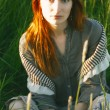 Sad redhead woman in grass — Stock Photo #7229213