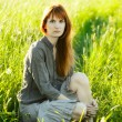 Sad redhead woman in grass — Stock Photo #7650046