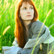 Sad redhead woman in grass — Stock Photo #7650152