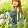 Sad redhead woman in grass — Stock Photo