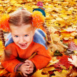 Girl child in autumn orange leaves. — Stockfoto