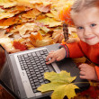 Girl child in autumn orange leaves with laptop. — Stock Photo