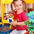 Child with puzzle, block and construction set in play room. - Stock Photo