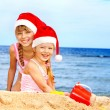 Foto Stock: Children in santa hat playing on beach.