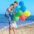 Child playing with balloons at the beach — Stock Photo #7110746