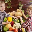 Foto Stock: Child with vegetable on kitchen.