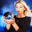 Foto Stock: Young woman with crystal ball.