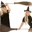 Two Halloween witch in black dress and hat on broom banner. — Stock Photo #7111324