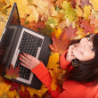 Girl in autumn orange leaves with laptop. — Stock Photo #7111452