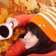 Girl in autumn orange leaves with cup coffe. — Stock Photo #7111453