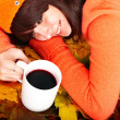 Girl in autumn orange leaves with cup coffe. — Stock Photo #7111454