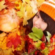 Girl in autumn orange leaves with pumpkin. — Stock Photo #7111459