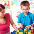 Child with wood block and construction set in play room. — Stock Photo #7111976
