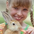 Stock Photo: Girl feed rabbit with carrot.