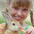 Girl feed rabbit with carrot. — Stock Photo