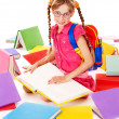 Happy sitting schoolgirl in eyeglasses with pile of books. — Stock Photo #7112053