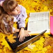 Kid in autumn orange leaves with laptop. — Stock Photo #7112087