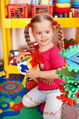 Child with puzzle, block and construction set in play room. — Stock Photo