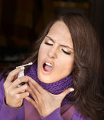 Woman using throat spray. — Stok fotoğraf