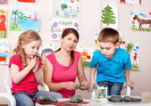 Children playing with teacher from clay. — Stock Photo
