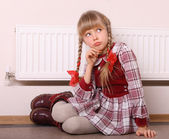 Regret girl sitting near radiator. Warmth depression. — Stock Photo