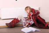 Girl lie on floor near radiator with book. — Stock Photo