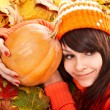 Girl with pumpkin on autumn leaves. — Stock Photo