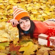 Girl in autumn outdoor holding gift box. — Stock Photo