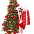 Christmas girl in santa hat and fir tree with red gift box. - Stock fotografie