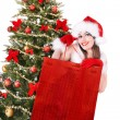 Christmas girl in santa hat giving  gift box. - Stock fotografie