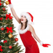 Girl in santa hat holding christmas ball. - Foto Stock