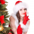 Girl in santa hat making silence gesture. Girl shushing. - Foto Stock