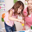 Child with teacher draw paints in play room. - Stock Photo