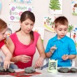 Stock Photo: Children mould with teacher from clay.