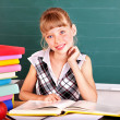 Stock Photo: Schoolchild in classroom near blackboard.