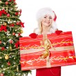 Girl in santa hat holding  gift box by christmas tree. — Stock Photo