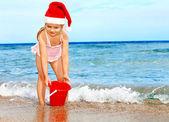 Child in santa hat playing on beach. — Stockfoto