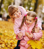Kids in autumn orange leaves. — Stock Photo