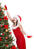 Girl in santa hat holding christmas ball. — Stock Photo