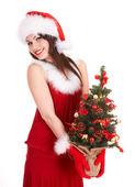 Garota de natal no chapéu de papai noel com pequena árvore na mão. — Foto Stock