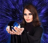 Girl with fortune telling ball against star sky. — Stock Photo