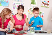 Children mould with teacher from clay. — Stock Photo