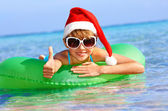 Child in santa hat floating on inflatable ring in sea. — Stock Photo