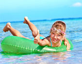 Kid sitting on inflatable ring thumb up. — Stock Photo