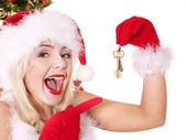 Christmas girl in santa hat holding house keys. — Stock Photo