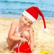 Child in santa hat playing on  beach. — Photo
